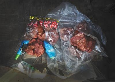 """一名黑作坊老板带了两袋""""驴肉""""给记者看货,左边一袋为冷冻马肉,右边一袋实为猪肉(图片:《新京报》)"""