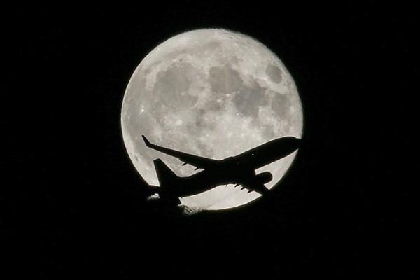 """乘坐""""赏月航班"""",飞机上的乘客可以幸运地透过机窗近距离欣赏到美丽的满月。 IC 资料图"""